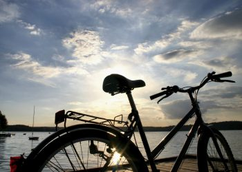 Silhouette of bycicle against lake