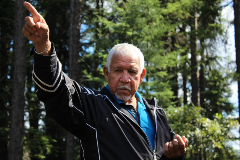 First Nations man holds hid arm up in a forest
