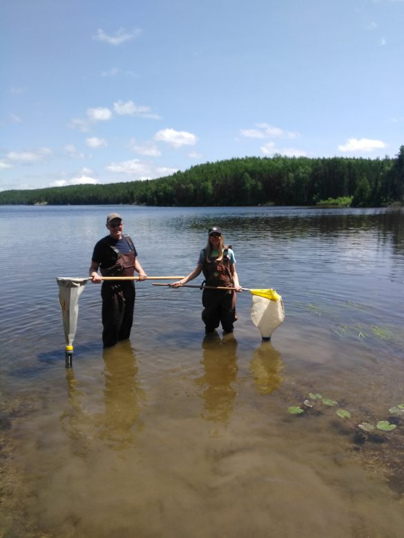 Man and female teenager stand in lake with waders, holding fishing nets.