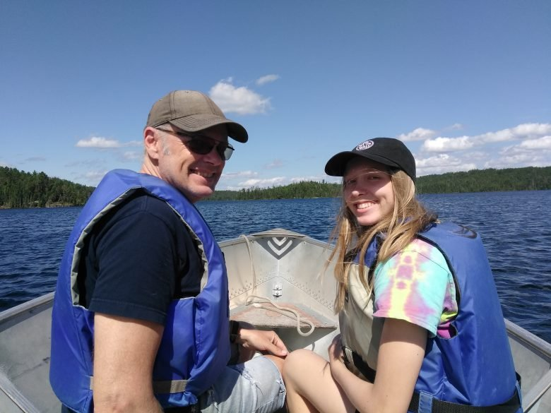 Man and female teenager sit on boat, looking at the camera.