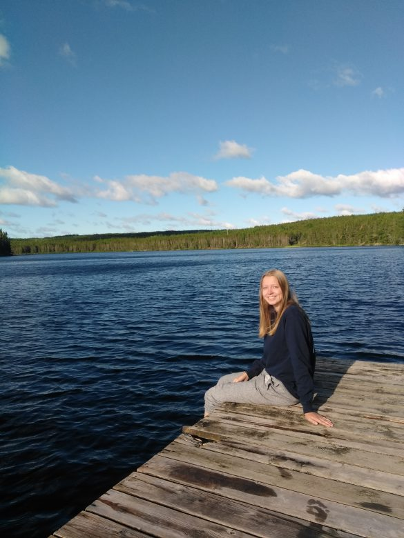 Female teenager sits on dock of lake looking at the camera.