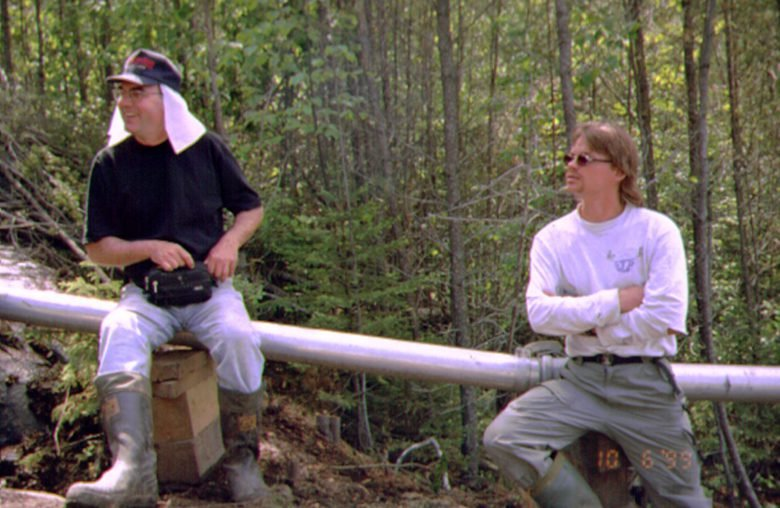 Two men sit on a metal beam at the Experimental Lakes Area