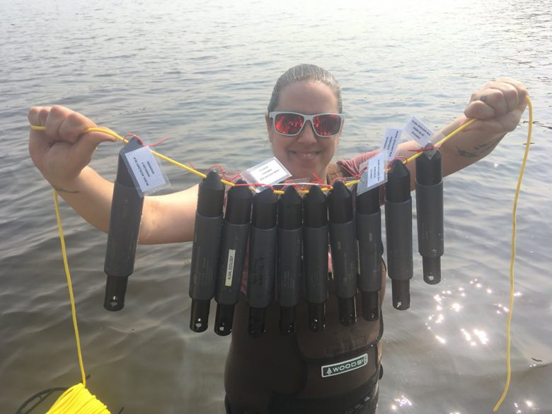 Female researcher holds a line of oxygen temp sensors out in front of her as she stands in front of a lake.