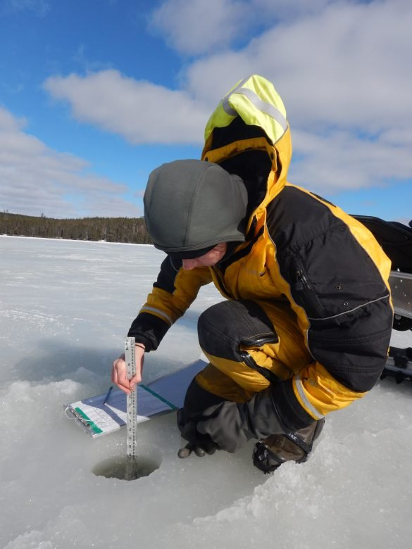 Scientists kneels down on a frozen lake while measuring a hole in the lake using a ruler.