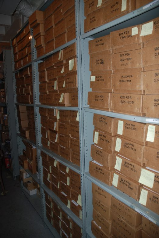 Grey shelved with hundreds of brown boxes with yellow Post-It notes.