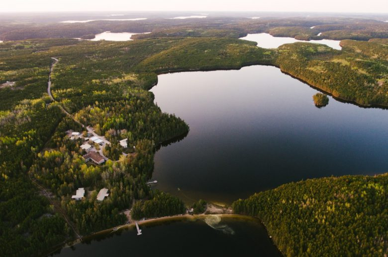 Aerial shot of a blue and silver freshwater lake surrounded by green trees and a few white buldings