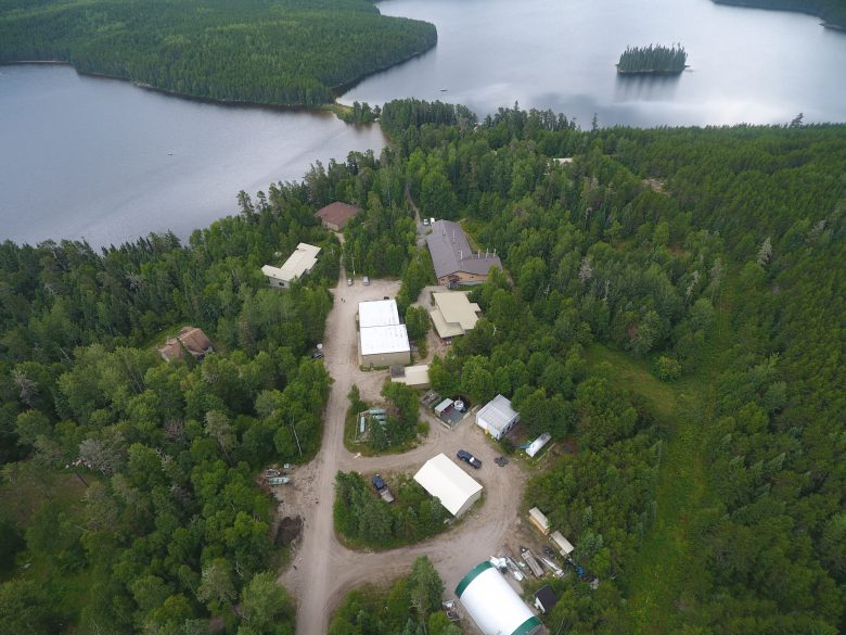 Aerial shot of a series of white buildings and cabins surrounded by green trees and lakes