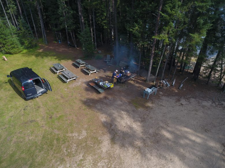 Aerial shot of a BBQ and dinner tables with a black van with its back door open.