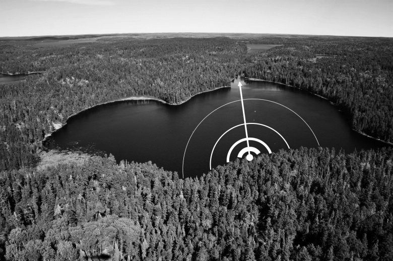 Black and white photo of a freshwater lake surrounded by trees and a white line and half circles