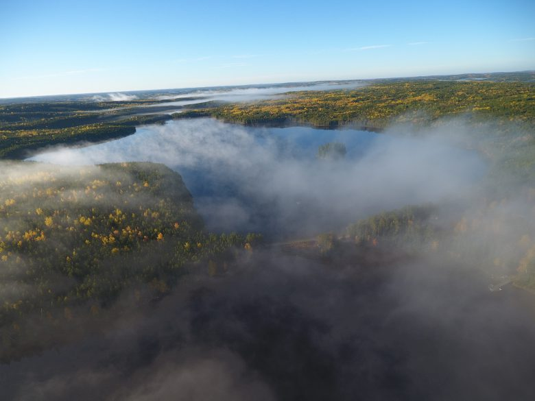 Aerial shot of morning mist over a freshwater lake bordered by forests
