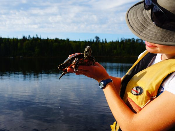 Woman wearing a hat and yellow vest holds a turtle and stands on a boat in a freshwater lake set against green trees.