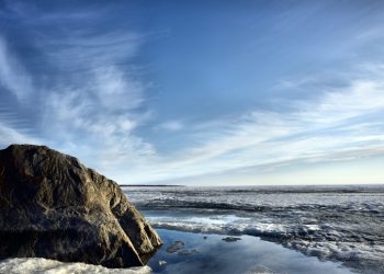 Large rock in foreground of Lake Winnipeg shoreline with waves