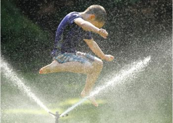 Young boy jumps through water from a sprinkler