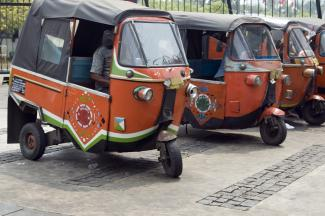 a row of small red rickshaws parked on a street.