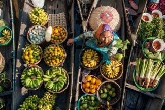 An overhead shot of a woman in a boat full of produce.