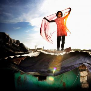 Little girl standing on a shack (in a slum). Sunlight is behind her.