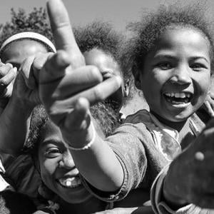 A closeup group of children smiling, throwing hand gestures to the camera.