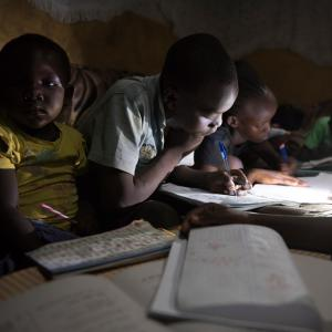 A group of children gathered around books, using a flashlight to read more clearly.