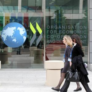 Two women walking in front of a building with the OECD logo.