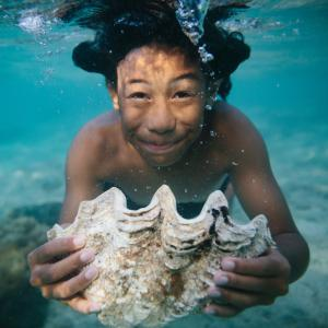 Boy swimming under water with a large sea shell.