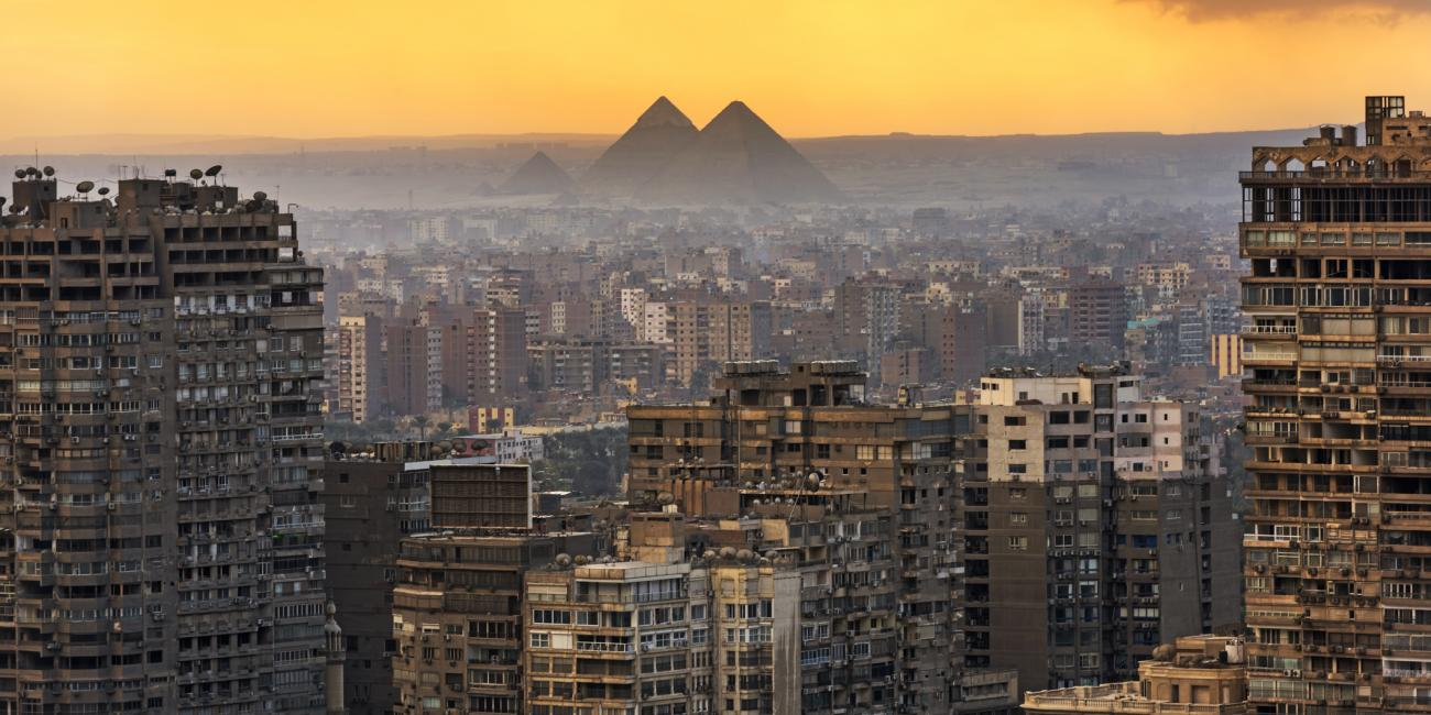 a birds eye view of a city in Egypt with a beautiful yellow sunset.