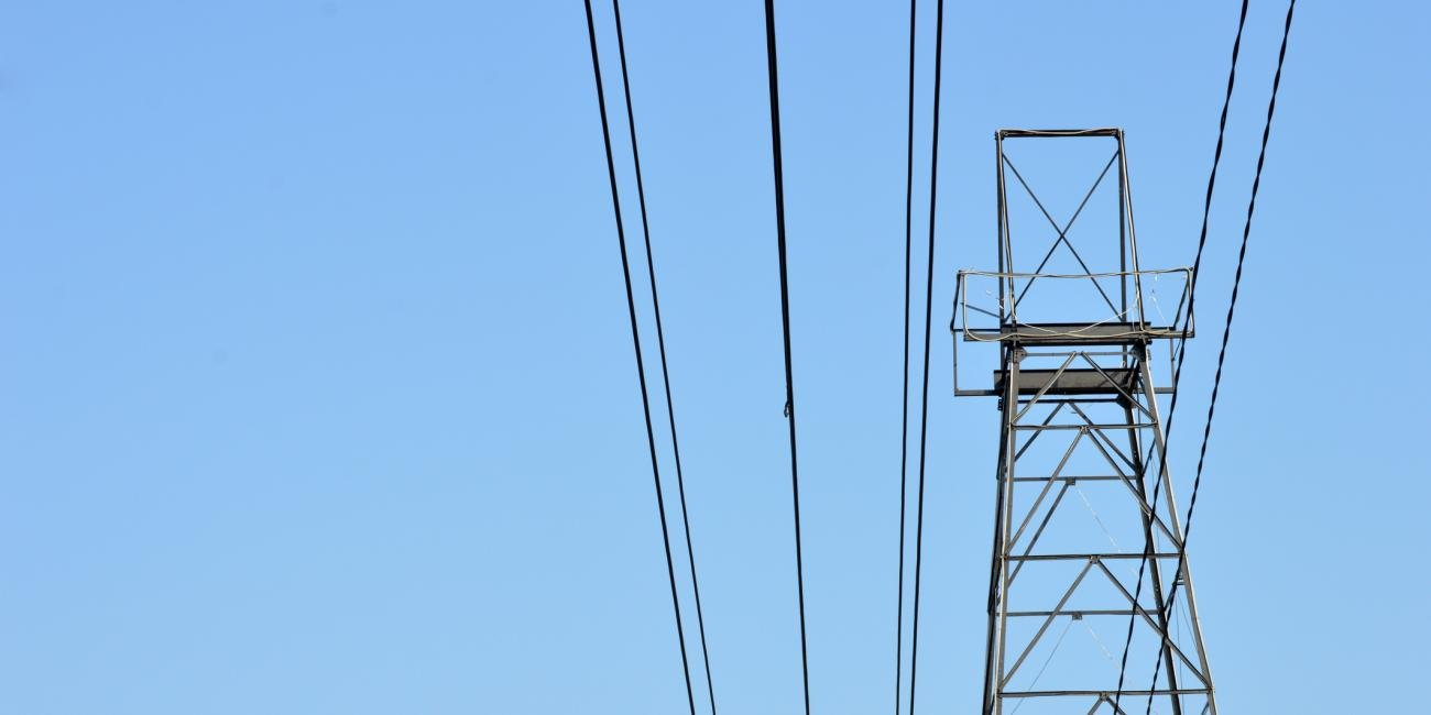 A power line and metal power pole with a clear blue sky as a background.