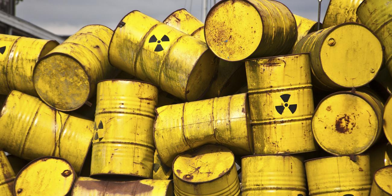 Large yellow chemical drums stacked in an unorganized fashion.