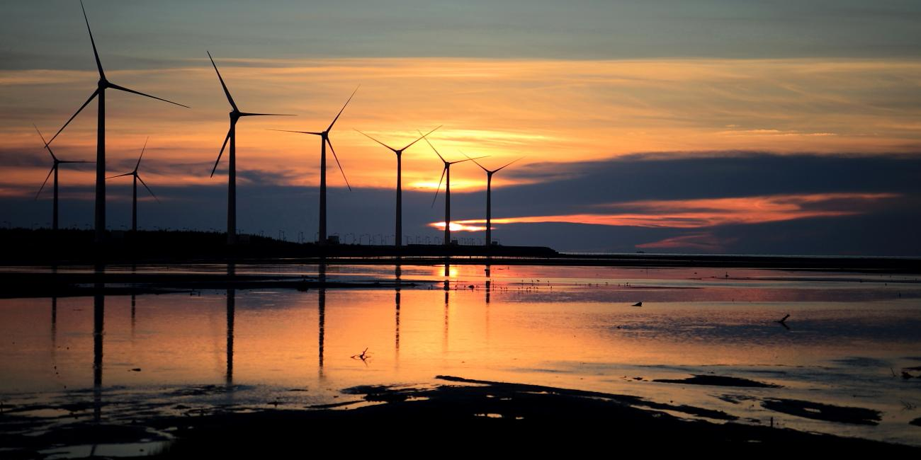 Windmills along the waterline at sunset.