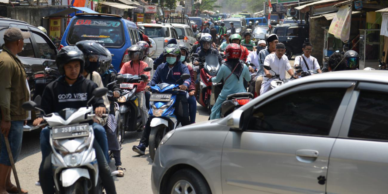 Men and women on motorcycles in a busy urban street in Jakarta, Indonesia, with some wearing face masks to protect from viruses and pollution.