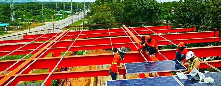 Workers adding solar panels on a construction site