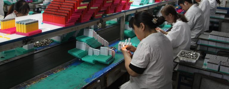 Workers assembling and testing lighters in factory in China