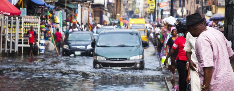 Cars drive down flooded market street in Lagos, Nigeria, with people crowded on either side.
