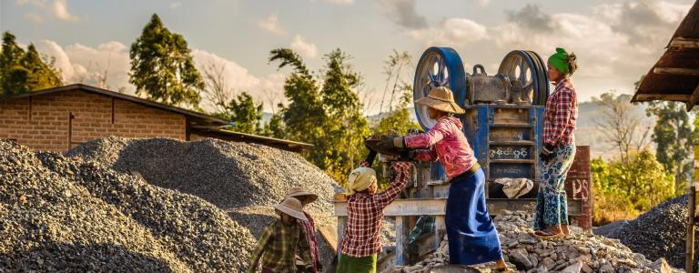 Three women work at an artisanal mine in Asia at dusk