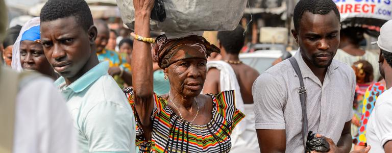A woman carries a large sack on her head while walking through a busy market, flanked by two men