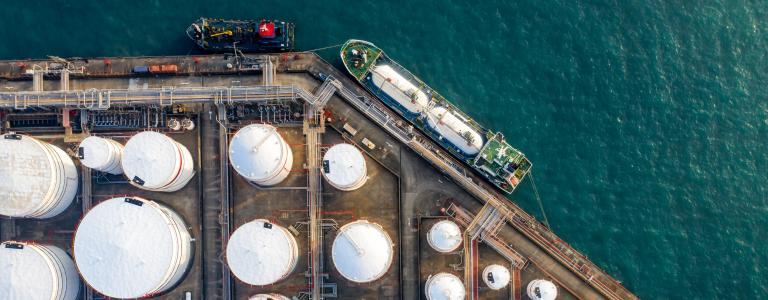 Oil refinery storage units with tanker ship viewed from above