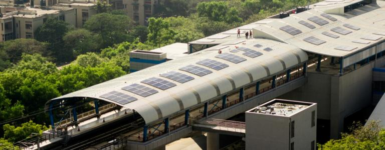 An aerial view of a metro station in Delhi with solar panels on the roof