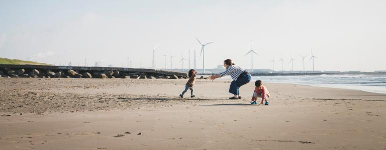 A mother and her two small children play on a beach with wind turbines in the distance