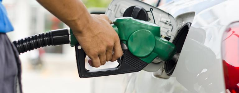 A hand filling a car with gas using a green nozzle