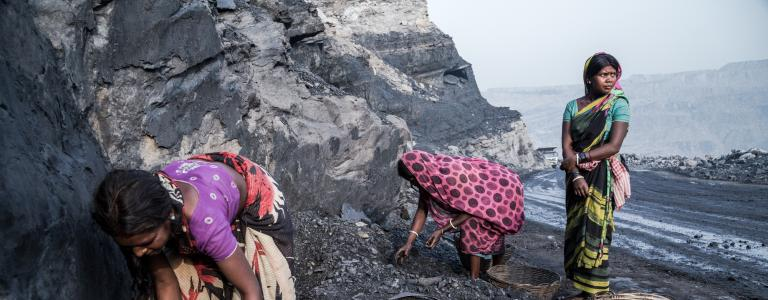 Three women work in a coal mine in traditional Indian dress