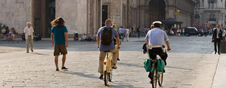 Two cyclists ride along a quiet street in Milan, Italy, seen from behind