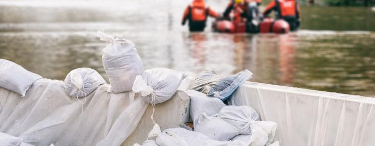 close-up of white sandbags holding back flood water with rescuers in a lifeboat in the background