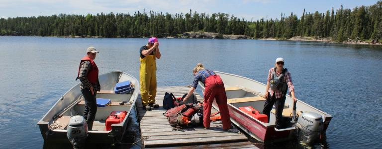Four scientists stand in two boats floating on a lake on a sunny day