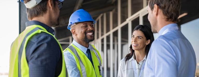 A Black man in construction hat and vest shakes hands with a man in a dress suit while smiling