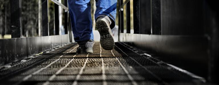 Worker walks along steel walkway.