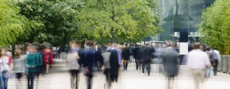 A crowd of blurry people walk underneath some trees in front of a glass building