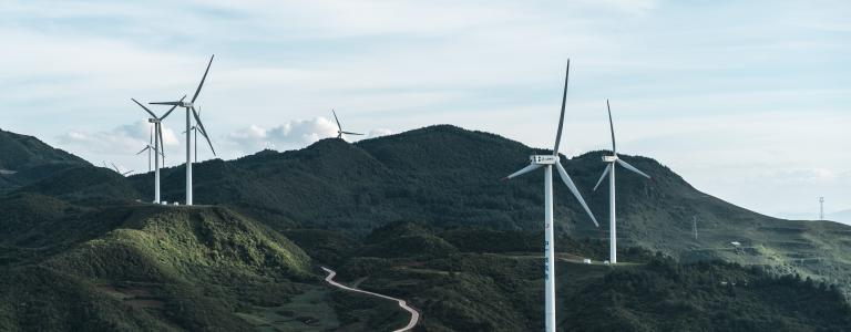 Wind turbines on rolling green hills and a blue sky