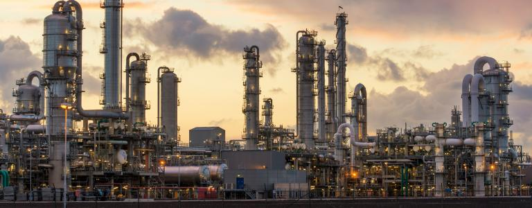 An oil refinery billows smoke against a dusk sky