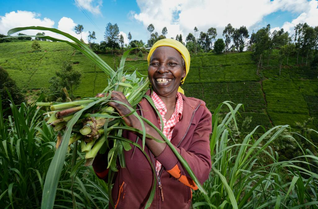 A smiling woman holds a vegetable crop