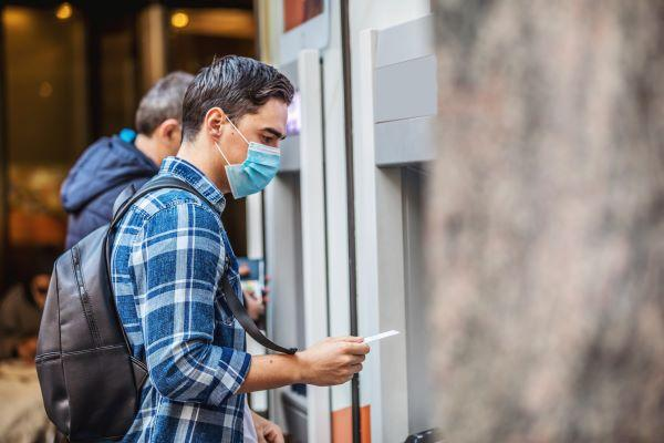 Man wearing an n95 mask using an ATM