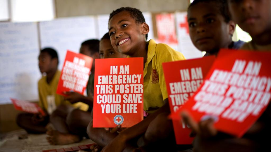 Students in a classroom in Fiji hold disaster risk reduction posters